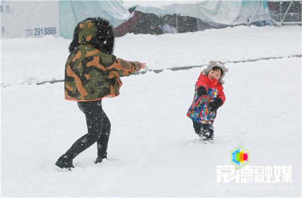 30日上午,万达广场,小朋友在开心的打雪仗。 李龙摄.jpg