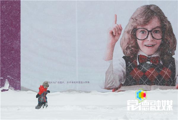 """30日上午,万达广场,小朋友在雪地上玩耍,巨型广告仿佛在告诉所有人""""下雪了""""  李龙摄.jpg"""